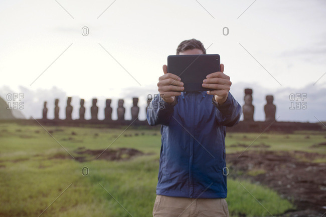 Man taking a selfie in front of maoi statues on Easter Island