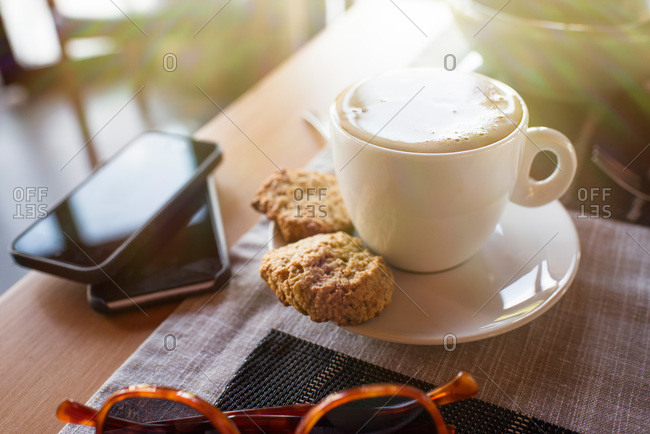 Coffee and cookies next to smartphones