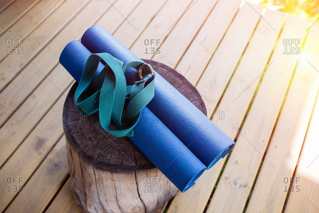 Yoga mats and strap on a wooden log