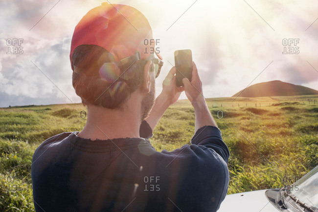 Man taking a photo of a landscape with his smartphone on Easter Island