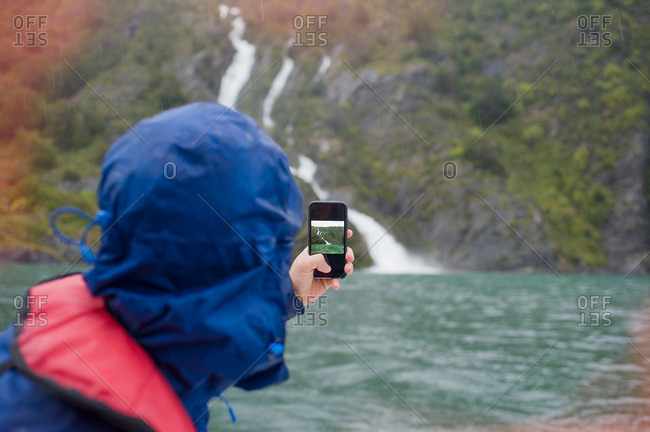 Tourist photographing a coastal waterfall in Patagonia