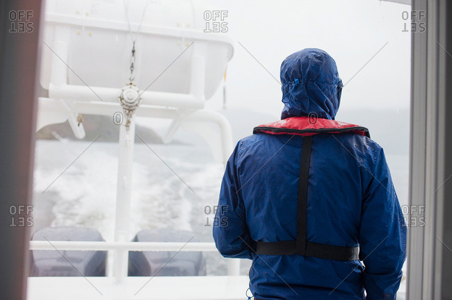 Man dressed in rain gear on a tour boat in Patagonia