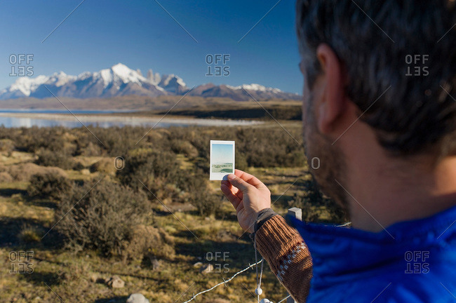 Man comparing photograph to the real view of a mountain in Patagonia