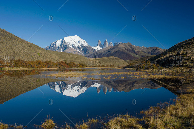 Snow covered mountains reflected in a lake in Patagonia