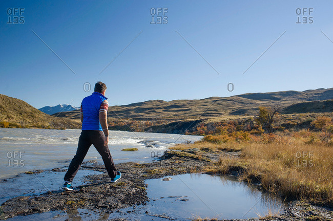 Man traversing a stream in Patagonia