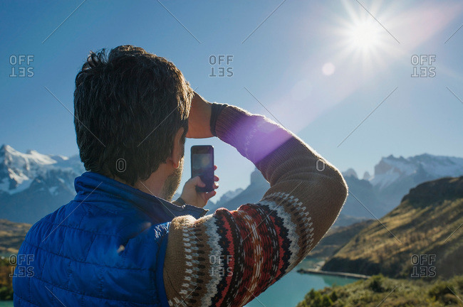 Man photographing landscape with a smartphone in Torres del Paine, Patagonia