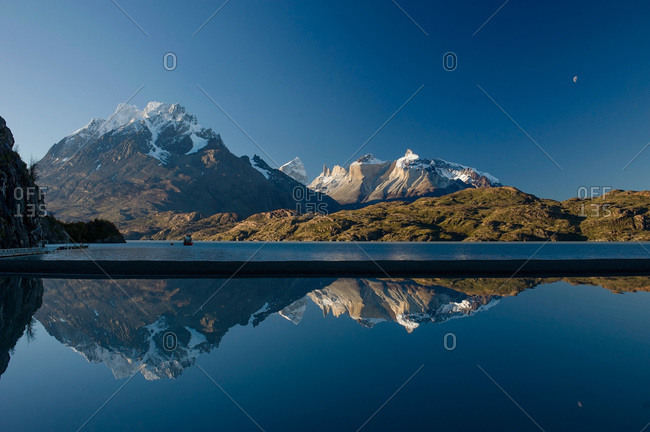 View of snow capped mountains and moon over water in Patagonia