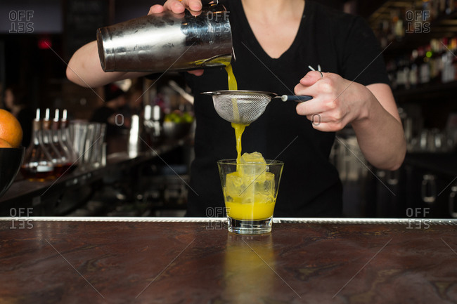Bartender making a yellow cocktail
