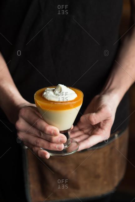 Server holding butterscotch custard dessert
