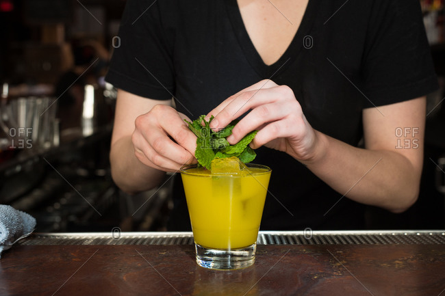 Bartender making a yellow cocktail with mint leaves