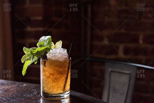 Cocktail with mint garnish sitting on bar