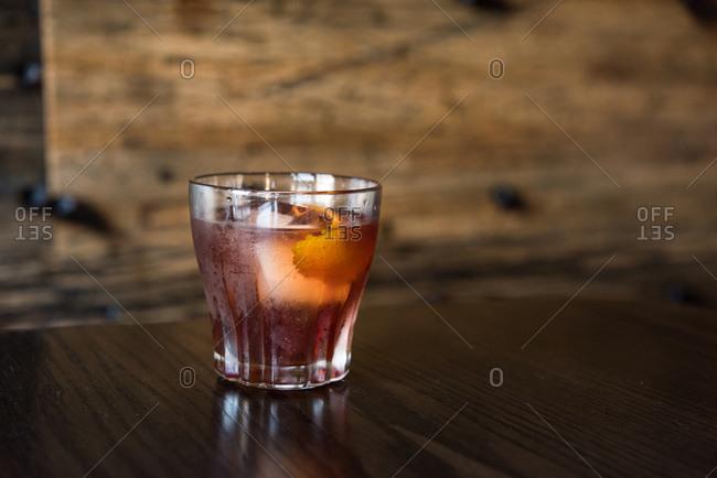 Cocktail with lemon peel garnish sitting on bar