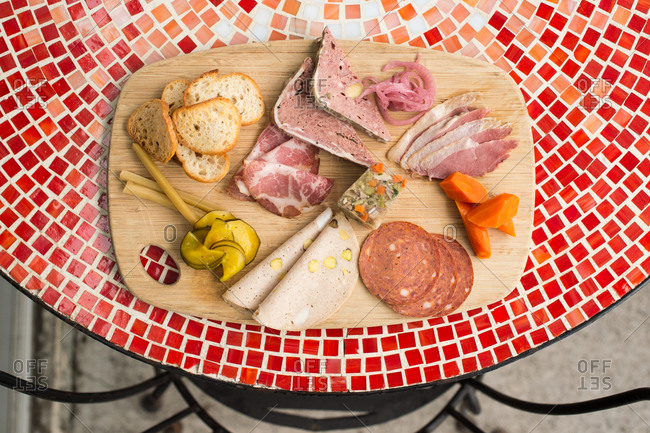 A cutting board with charcuterie on a red tile table