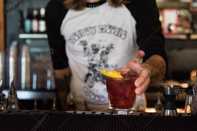 Tattooed bartender serving cocktail with lemon garnish