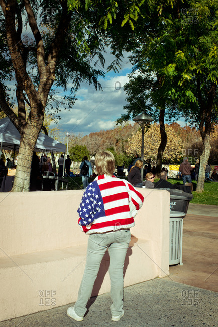 Woman in American flag coat watching community event