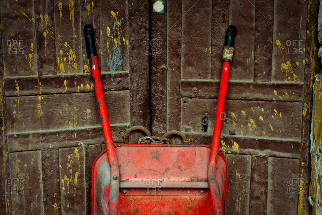 Wheelbarrow propped against doors