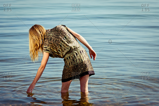 Woman touching surface of water