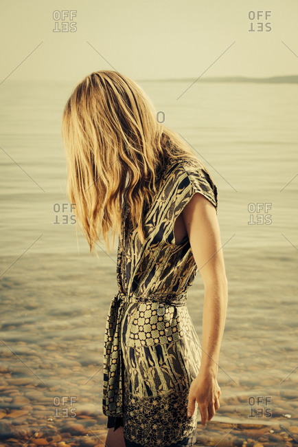 Woman with hair covering face on beach
