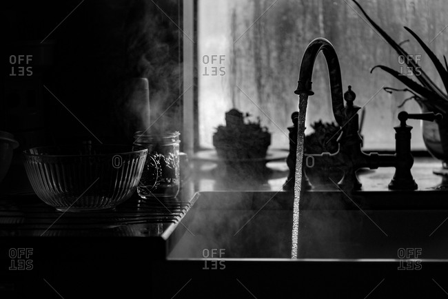 Steaming water pouring out of the kitchen faucet
