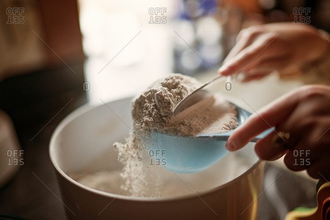 Girl leveling flour in a measuring cup