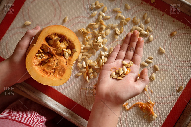 Girl picking seeds out of a pumpkin