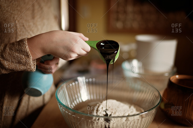 Girl pouring molasses into bread mixture