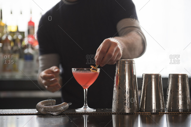 Bartender garnishing a pink cocktail