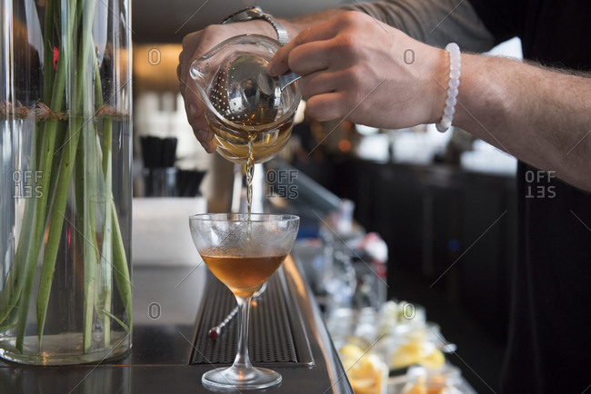 Bartender pouring a Manhattan cocktail