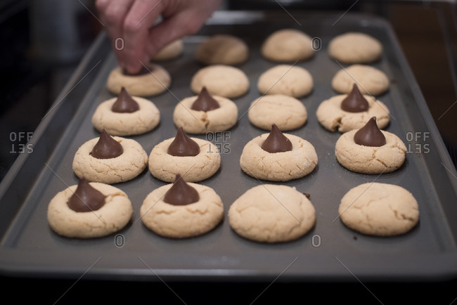 Hand putting chocolate candies on cookies