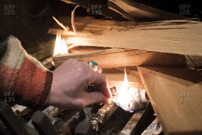 Man lighting a fire in a fireplace