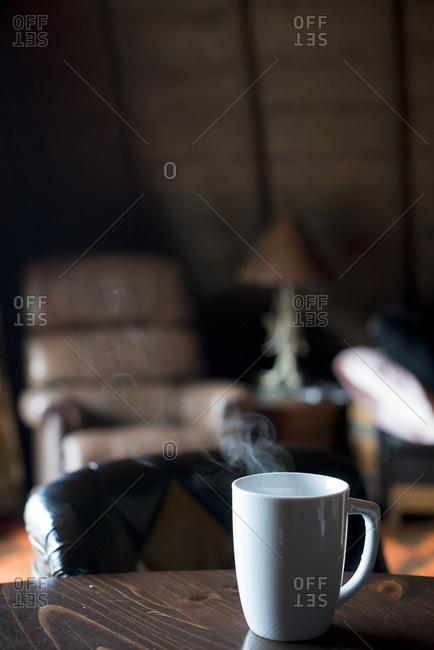 Mug of coffee steaming on a living room table