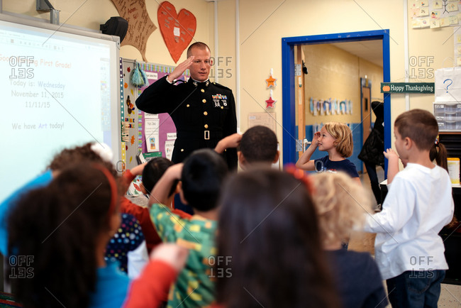 Children saluting a veteran visiting their classroom