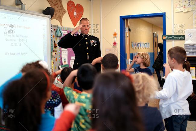 Children saluting a veteran visiting their classroom