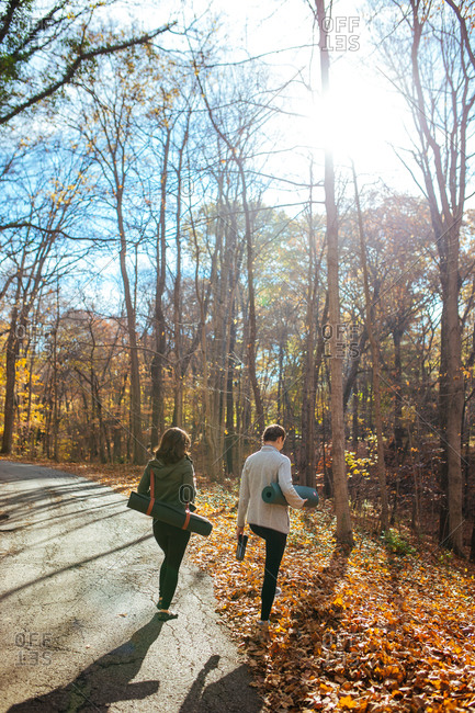 Two women walking off of a path into the woods with yoga mats