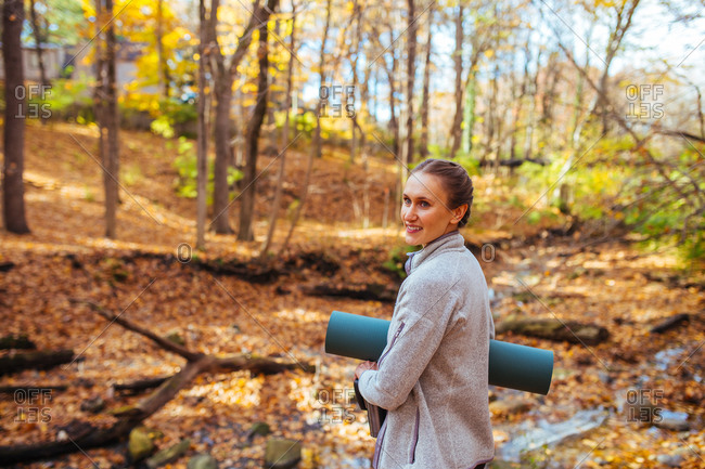 Woman walking into the woods with yoga mat