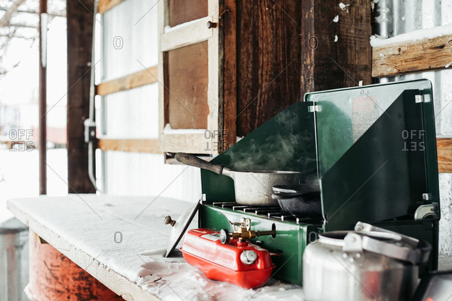 Pots and pans on a camp stove on a snow covered bench