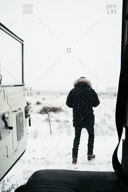 Back view of person standing in the snow outside of vehicle
