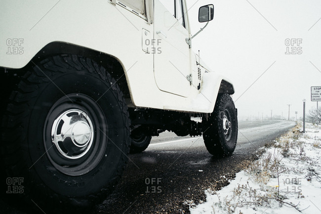 Close-up view of a sports utility vehicle on the side of an icy highway