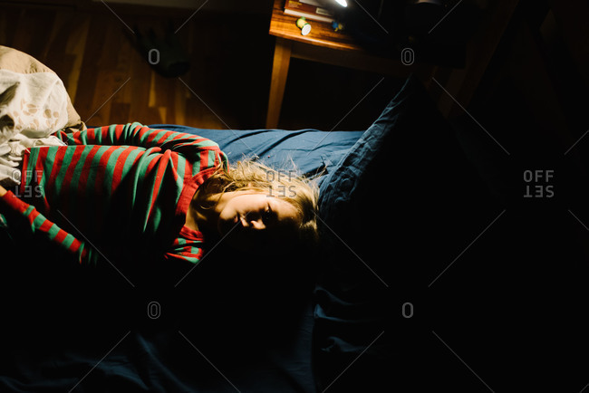 Overhead view of child in striped pajamas lying in bed