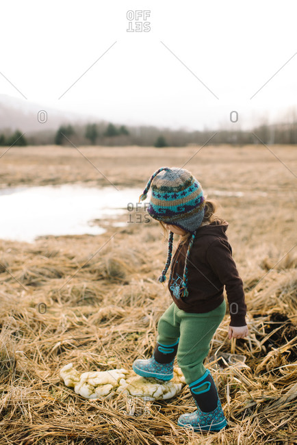 Toddler girl stepping on chunk of ice in field