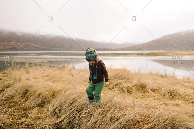 Toddler girl exploring long grass in marshy landscape