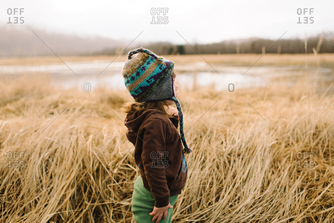 Toddler girl standing in long grass in marshy landscape