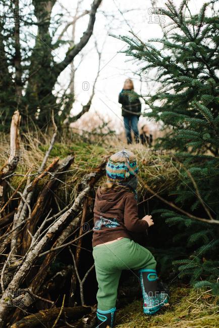 Toddler girl climbing up embankment in woods