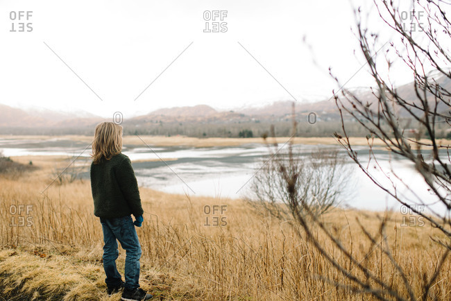 Boy gazing off into distance near tidal flat