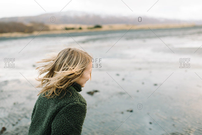 Young boy with long blond hair on a tidal flat