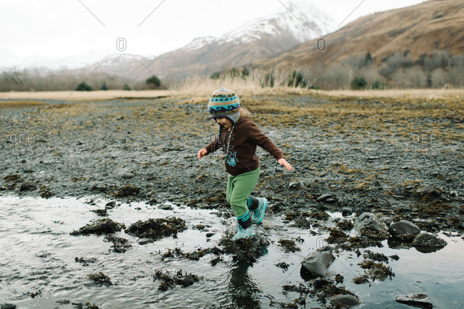 Toddler girl splashing in stream of water in tidal flat