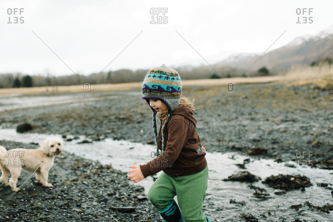 Toddler girl and pet dog playing on tidal flat