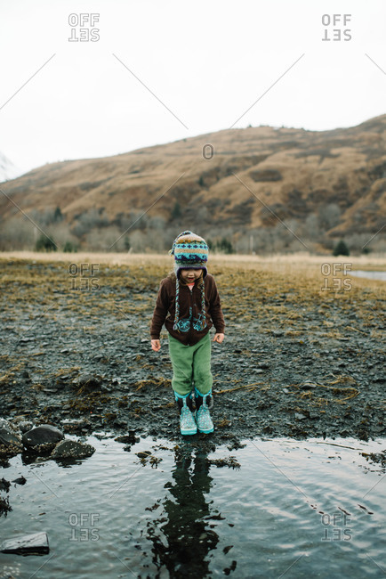 Toddler girl in rubber boots standing at edge of water