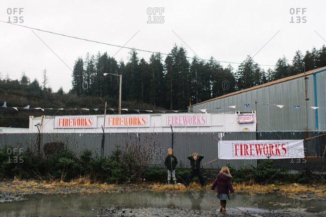 Kids standing next to rural fence with fireworks sign