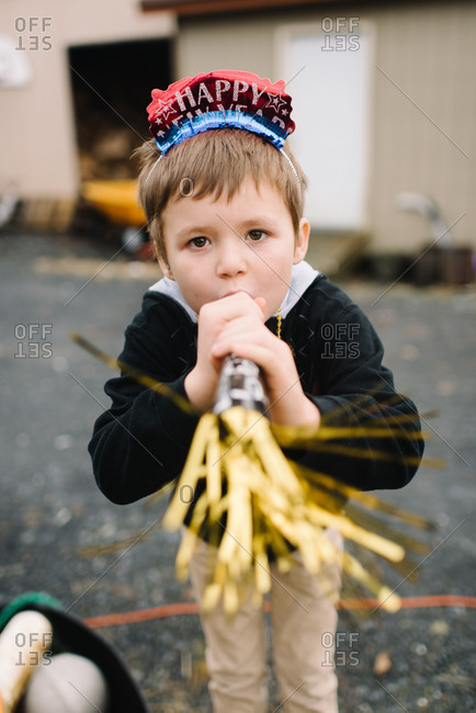Boy in New Year\'s headband blowing party horn